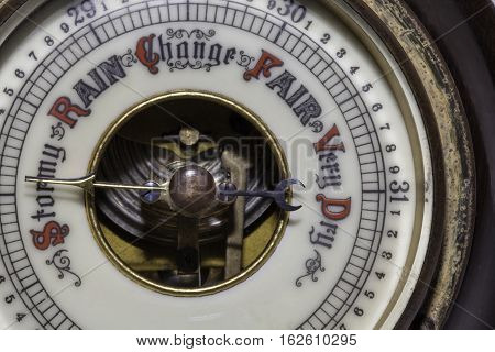 Slightly simplified image of a vintage weather barometer forecasting stormy weather ahead.