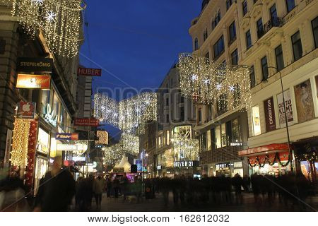 VIENNA, AUSTRIA - JANUARY 1 2016: Night view of Kartner street in Vienna at winter time with Christmas decoration and many people around