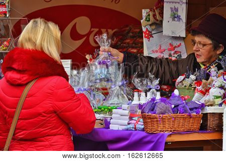 CLUJ-NAPOCA ROMANIA - DECEMBER 17 2016: Vendor hands over a gift package to buyer at the market. Blond woman shops cosmetics packed in cellophane