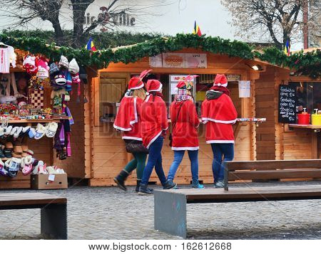 CLUJ-NAPOCA ROMANIA - DECEMBER 17 2016: Girls dresses in Santa Claus costumes do shopping at the Christmas market.
