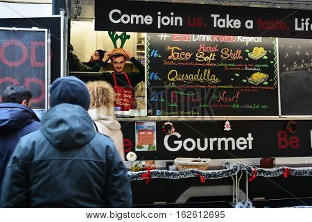 CLUJ-NAPOCA ROMANIA - DECEMBER 17 2016: People buy street food at the Street Food Festival winter edition. Food trucks sell tasty fast food from different cultures