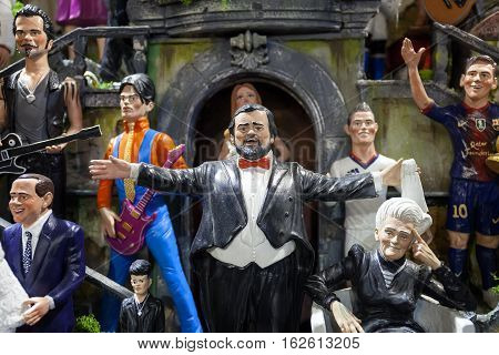 Naples Italy - December 9 2016: San Gregorio Armeno statuettes handmade representatives famous celebrities sports politics music and religion. In the foreground the opera singer Pavarotti bottom left Silvio Berlusconi right Rita Levi Montalcini