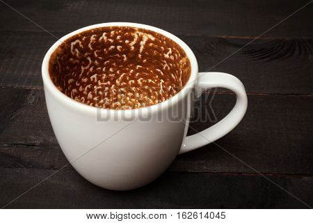 Finished Greek coffee cup on wooden black background