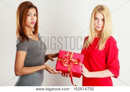 Occasions gifts people concept. Beautiful women blonde caucasian girl and mulatto with red gift box on gray