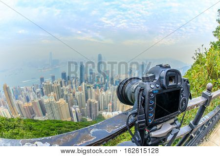 Close up of a professional camera on the tripod while photographing the Victoria Harbour from The Victoria Peak in Hong Kong. Fisheye lens with focus on the camera and background skyline blurred.