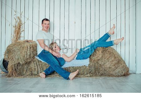Young Attractive Couple: Pregnant Mother And Happy Father Sitting On The Hay Sheaves Near White Wood