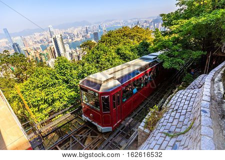 The popular red Peak Tram as he arrives at the terminus of Victoria Peak, the highest peak of Hong Kong island, with panoramic city skyline in background. Sunny day.