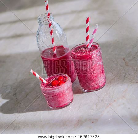 Juicy berry smoothies in glass, jars, bottles on marble background. Selective focus. Toning.
