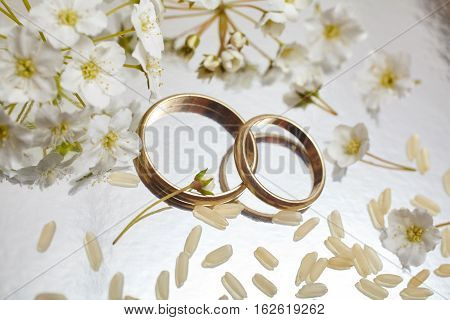 Gold wedding rings with flowers in studio