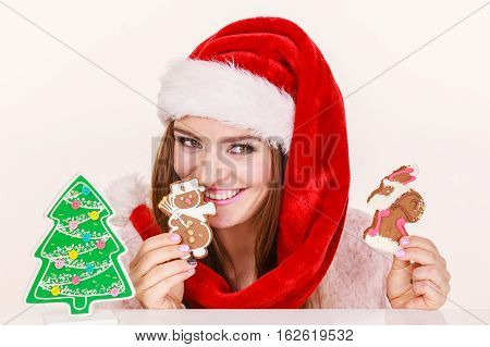 Woman wearing red xmas hat playing with gingerbread cookies little snowman and claus. Happy girl awaiting christmas holidays