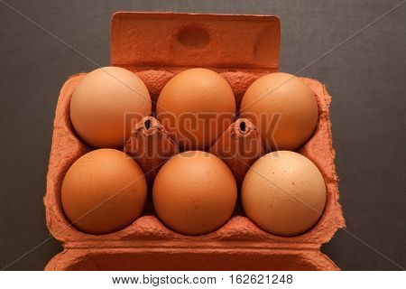 Eggs in the package on black background