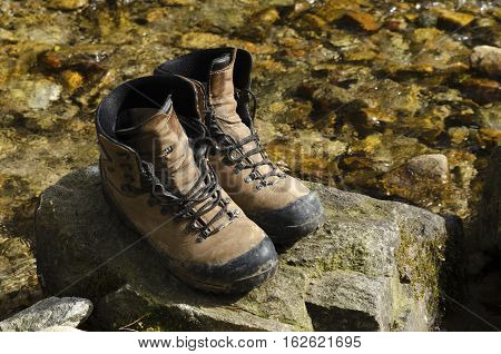 Old tourist hiking shoes in a river on a rock