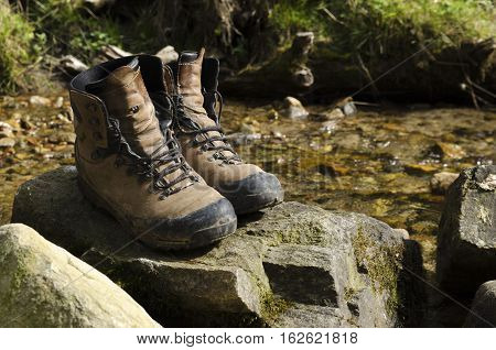 Old tourist hiking shoes on a rock in a river