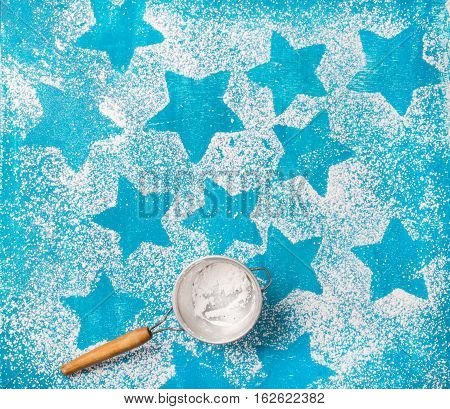 Sieve with sugar powder and star shaped biscuits silhouettes over bright blue background, top view, copy space