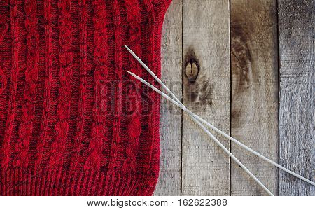 Beautiful red knitted sweater with needles on wooden background. Knitting texture. Knitting pattern. Copy space. Half.