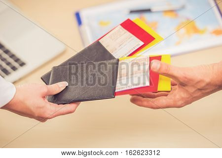Close-up of human hands holding tickets and passports while visiting travel agency poster