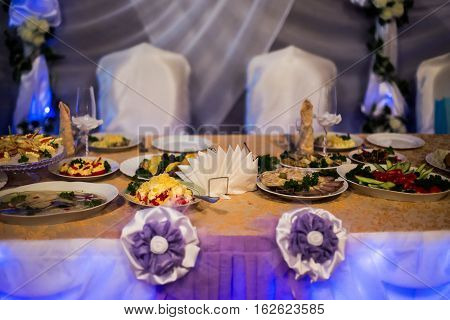wedding accessories wedding preparation decorated wedding table with flowers wedding flowersfood on the table decorated chairs table and chairs glasses salad on the table vegetables snack