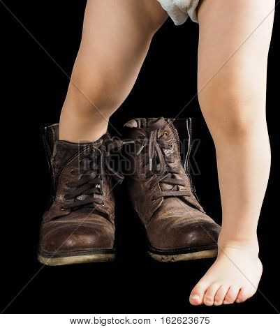 Toddler Boy, Towards Black Background In Fathers Brown Leather Boots