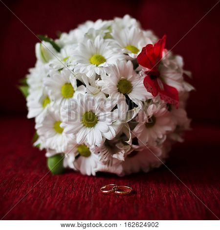 infinity sign of the rings wedding rings on a red backgroundwedding bands rings on a white background wedding flowers wedding bouquet bouquet of big beautiful daisies flowers on a red background red butterfly on flowers