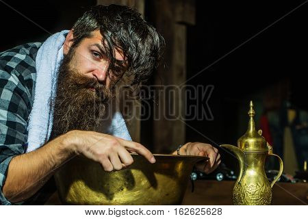 Handsome man hipster with beard washes hair in vintage copper basin in barber shop
