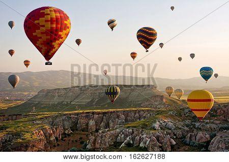 GOREME/ TURKEY - MAY 25, 2015: Hot air balloons take off in Cappadocia on may 25, 2015 in Goreme, Anatolia, Turkey. The great tourist attraction of Cappadocia - balloon flight.