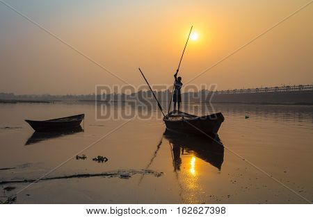 Silhouette boat with oarsman at sunset on river Damodar, Durgapur Barrage, West Bengal, India.