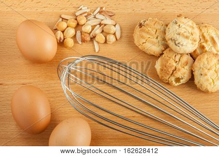 Tasty homemade cookies with fresh eggs ingredients mixed nut and metal whisk beater.