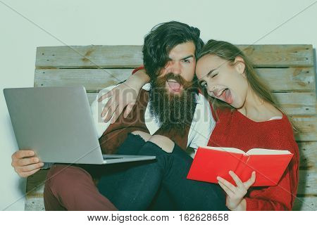 Young couple spend time together on wooden pallet sofa. Handsome man bearded hipster with beard uses laptop computer. Pretty winking girl or beautiful woman reads book