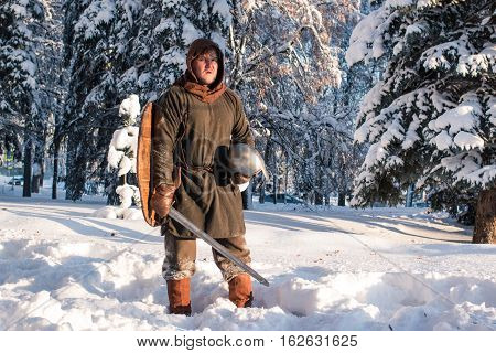 Warrior with swordin the winter forest in armor