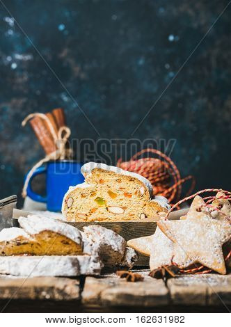 Piece of Traditional German Christmas cake Stollen with festive gingerbread star shaped cookies, selective focus, dark blue grunge background, copy space, vertical composition