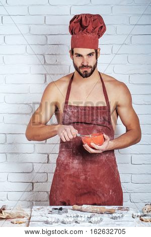Handsome man or muscular cook baker in red chef hat and apron with flour on sexy muscle torso body with biceps triceps beats dough by whisk on kitchen wall