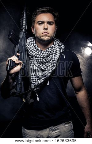 Soldier or mercenary wearing a shemagh with assault rifle paintball or airsoft gun. The image also depicts militarization of police or PMC private military companies