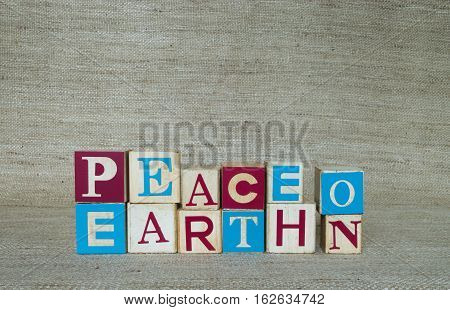 Blue, red and off white wooden blocks spelling peace on earth. Photographed against a tan cloth background in natural light at eye level.