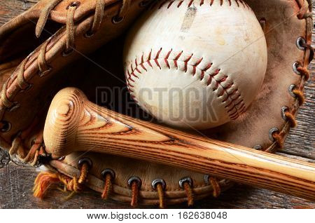 A close up image of an old used baseball glove and bat.