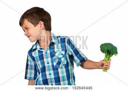 Young Boy Turning his Head with disgust away from a Broccoli Bunch
