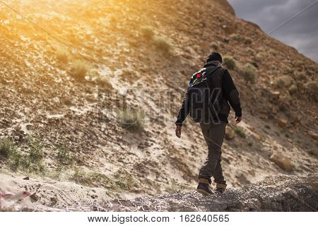Man walking on rock mountain. Backpacker and travel concept.
