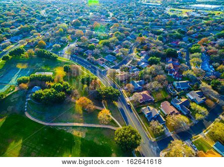 Above Autumn Colors Aerial on Suburbs Homes in Austin Texas near Round Rock hiking trails into Park and Fall leaves on trees with Lens Flare