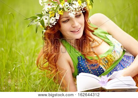 Beautiful girl in wreath and sundress lying on grass and reading a book