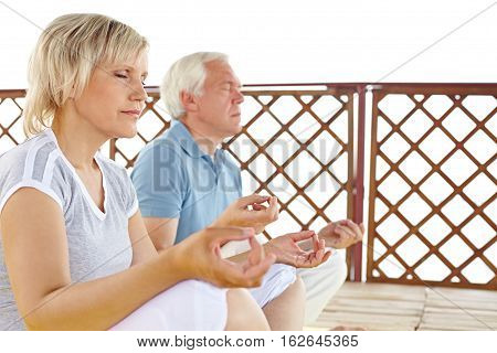 Senior wife and husband meditating on porch