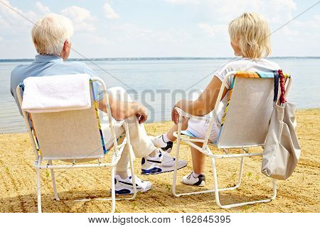 Rear view of senior couple sitting in chaise lounge chairs and admiring sea view