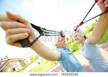 Cheerful senior couple exercising with resistance bands