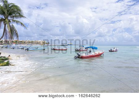PLAYA DEL CARMEN MEXICO - NOVEMBER 8 2016: Mexican panga fishing boats sit moored near the shore along the beautiful Mexican Riviera travel destination of Playa del Carmen.