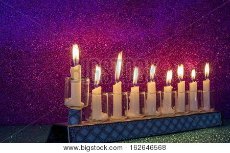Menorah with glitter light of candles is a traditional symbol for Hanukkah holiday