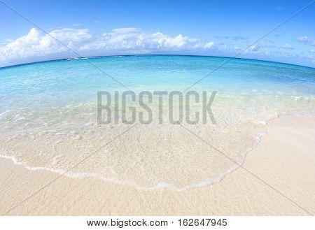 Fisheye view of Caribbean beach with beautiful sand turquoise water and speeding boat on horizon