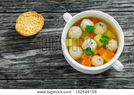 Chicken Soup With Meatballs, Carrot And Potato Sprinkled With Parsley
