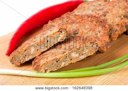 liver pancakes or cutlets with chilli and spring onions on a cutting board close-up isolated on white background.