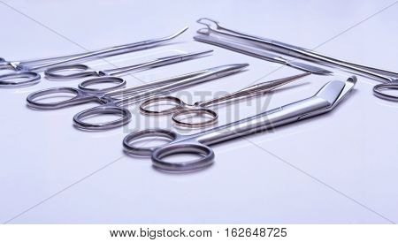 surgical instruments and tools including scalpels forceps and tweezers arranged on a table for a surgery. poster