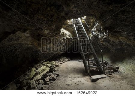 Ladder descending into underground Lave tubes at Lava Beds National Park