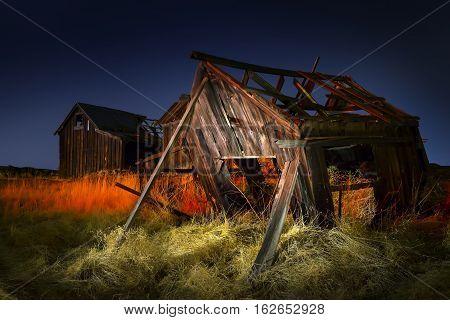 Old Abandoned fishing shacks at night light painted. The Dalles Oregon.