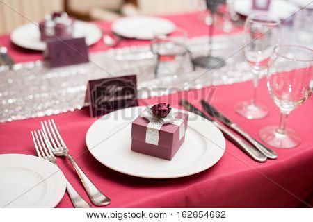 plate with a giftbox, red wedding decor, table of newly married